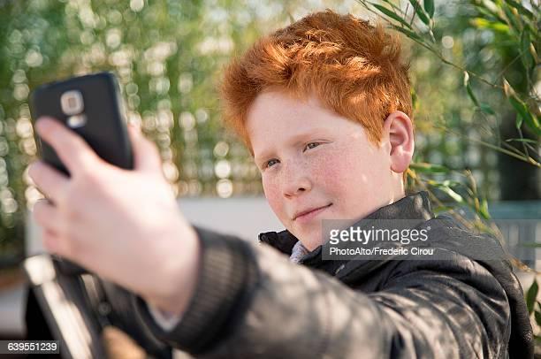 Boy using smartphone to take a selfie