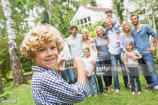Boy using smartphone with family in background