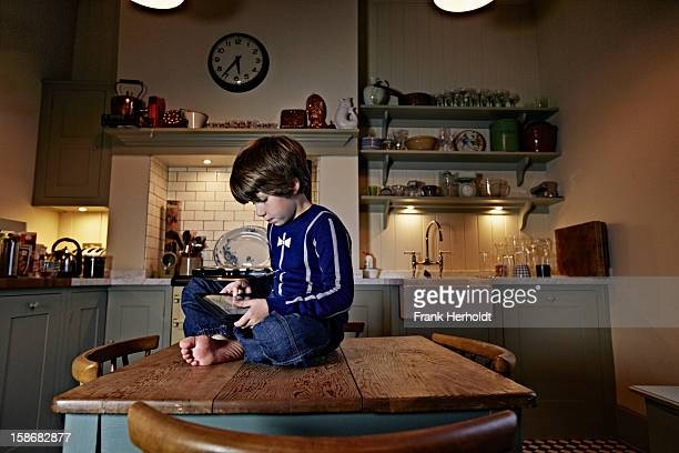 Boy using tablet computer sitting on kitchen table