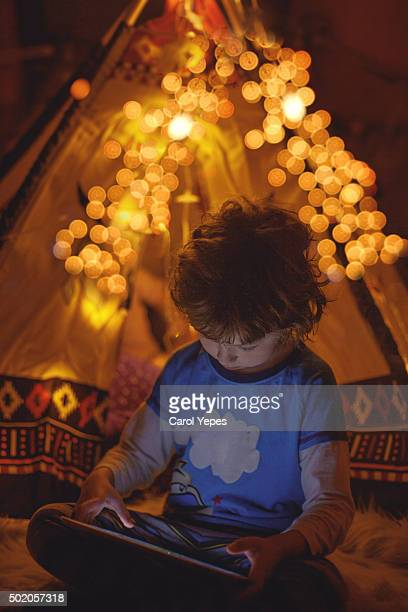 boy using tablet night - teepee stock pictures, royalty-free photos & images