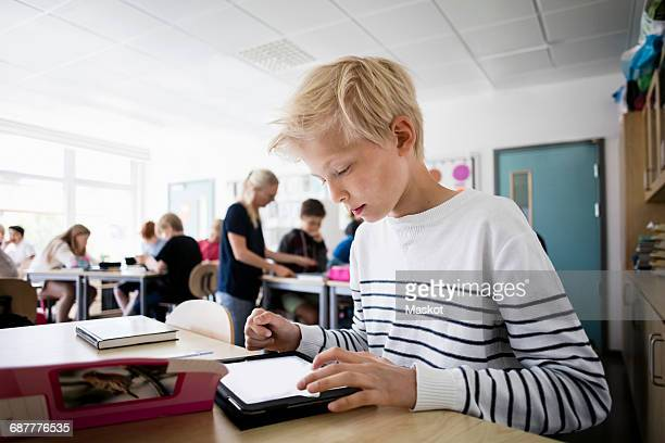 Boy using tablet pc at desk in classroom