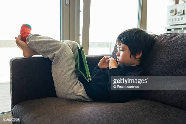 boy using tablet pc on sofa - peter lourenco stock pictures, royalty-free photos & images