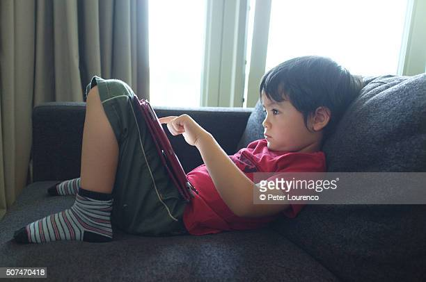 boy using tablet pc - peter lourenco ストックフォトと画像