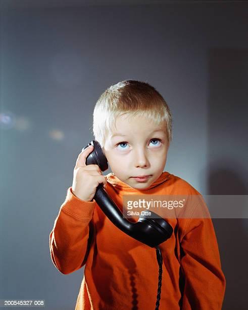 Boy (4-5) using telephone, looking upwards, close-up