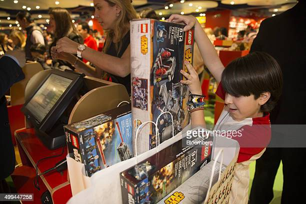 A boy views a Star Wars Lego toy just purchased during the opening of a new Hamleys Plc toy store at the Antara Mall in Mexico City Mexico on Monday...