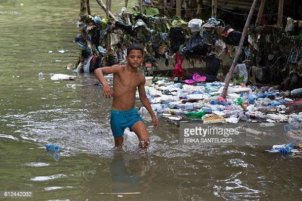 A boy wades through the water the flooded neighbourhood of La Puya in Santo Domingo on October 4 2016 after the passage of Hurricane Matthew through...