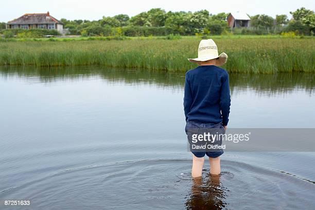 Boy wading in wetlands