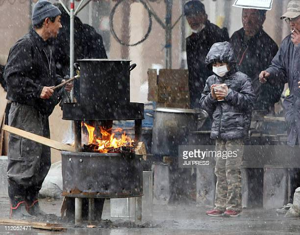 A boy waits for boiled water to cook instant noodle outside a shelter in Sendai in Miyagi prefecture on March 16 2011 A fresh fire broke out at the...