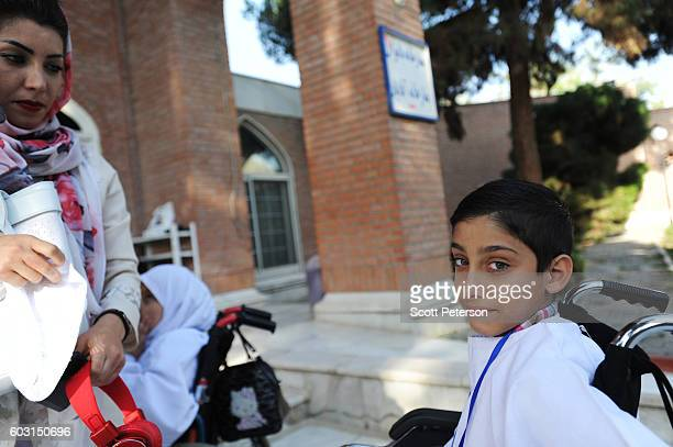 A boy waits for his mother as wheelchairbound Iranians prepare to reenact some parts of the Hajj pilgrimage as Iranians marked the Eid AlAdha Islamic...