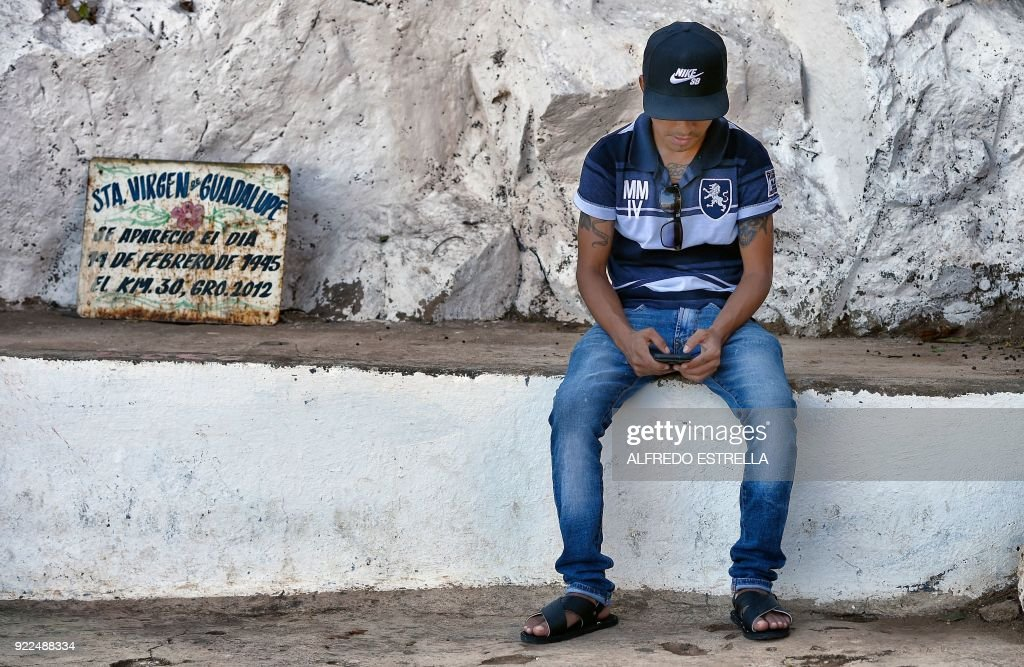 A boy waits next to a Guadalupe Virgin sign at Kilometro 30 community near the Acapulco resort in Guerrero State, Mexico on February 14, 2018. Violence in the state of Guerrero claimed the lives of two priests on February 5, 2018. / AFP PHOTO / Alfredo ESTRELLA / TO