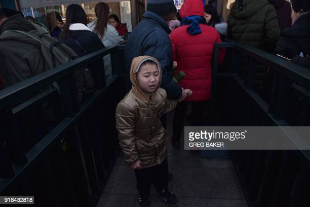 A boy waits with a relative before boarding a train at a railway station in Beijing on February 10 as travellers depart the capital ahead of the...