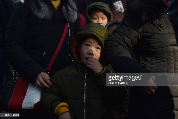 A boy waits with his family before entering a railway station in Beijing on February 10 as travellers depart the capital ahead of the Lunar New Year...