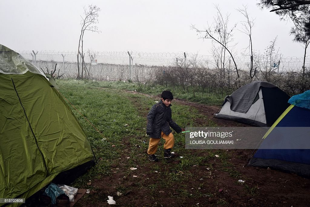 A boy walk past tents set up next to the border fence of the Greek-Macedonian border near the Greek village of Idomeni on March 4 2016 where thousands of ... & A boy walk past tents set up next to the border fence of the Greek ...