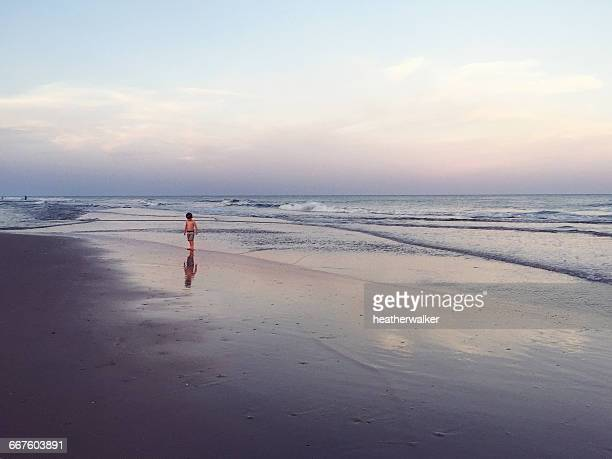 Boy walking along beach at dusk, Florida, America, USA