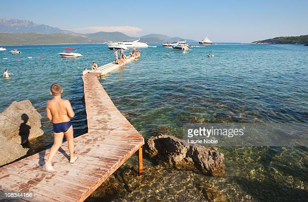 Boy walking along pier, Oblatno Beach