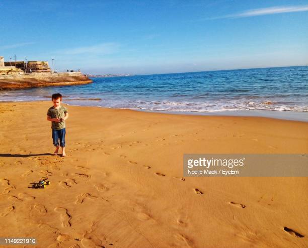boy walking at beach against sky - mack stock pictures, royalty-free photos & images