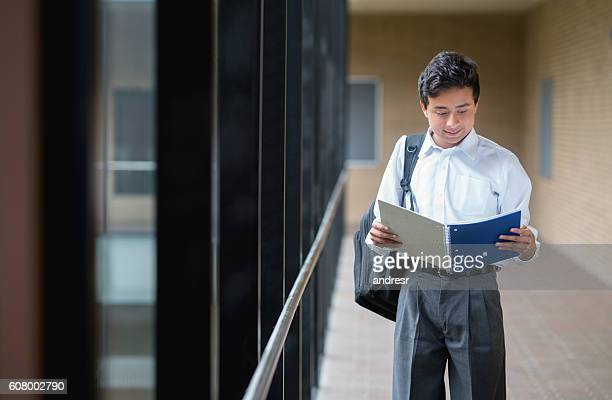 Boy walking at school looking at his notebook