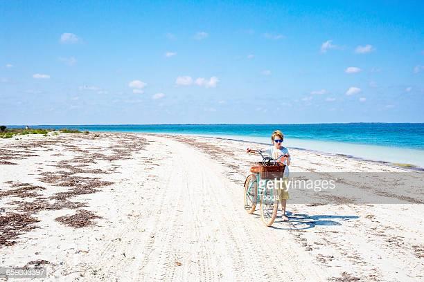 Boy walking bike on beautiful beach