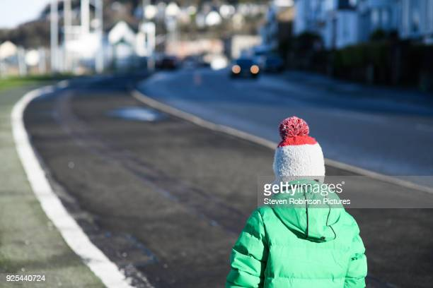 boy walking by road - winter coat stock pictures, royalty-free photos & images