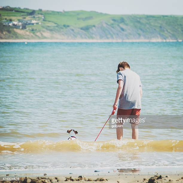 Boy walking dog at Weymouth Beach, Dorset England