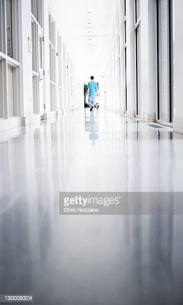 Boy walking down long white marble hallway