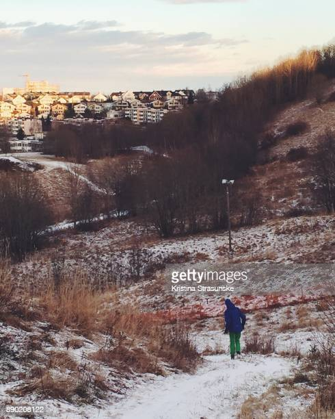 A boy walking happily down the hill on a sunny winter day