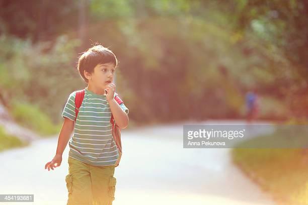Boy walking in a park looking away