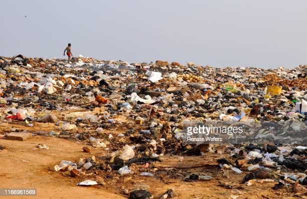 boy walking in garbage dump against clear sky - ghana africa fotografías e imágenes de stock