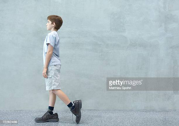 Boy walking in oversized shoes