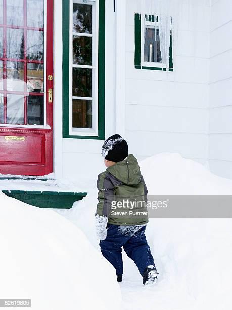 Boy (2-3) walking in snow to front door of home