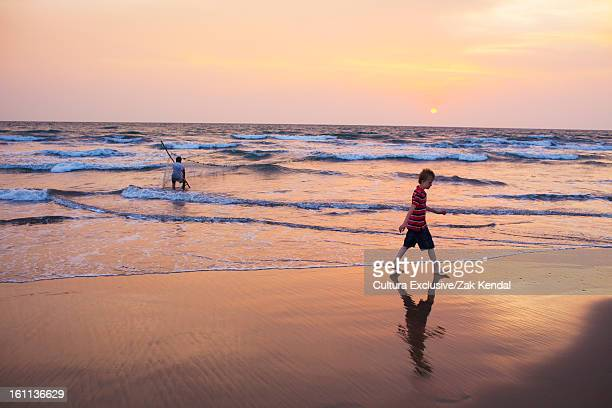 boy walking in waves on beach - goa stock photos and pictures