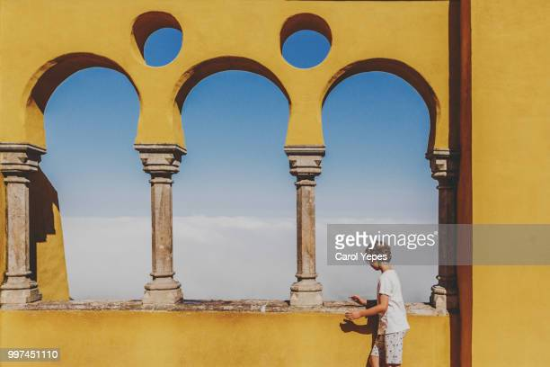 boy walking in yellow beautiful wall - sintra stock pictures, royalty-free photos & images