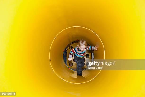 Boy walking inside yellow tunnel