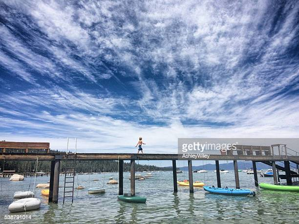 boy walking on a dock on lake tahoe in summer - lake tahoe stock photos and pictures