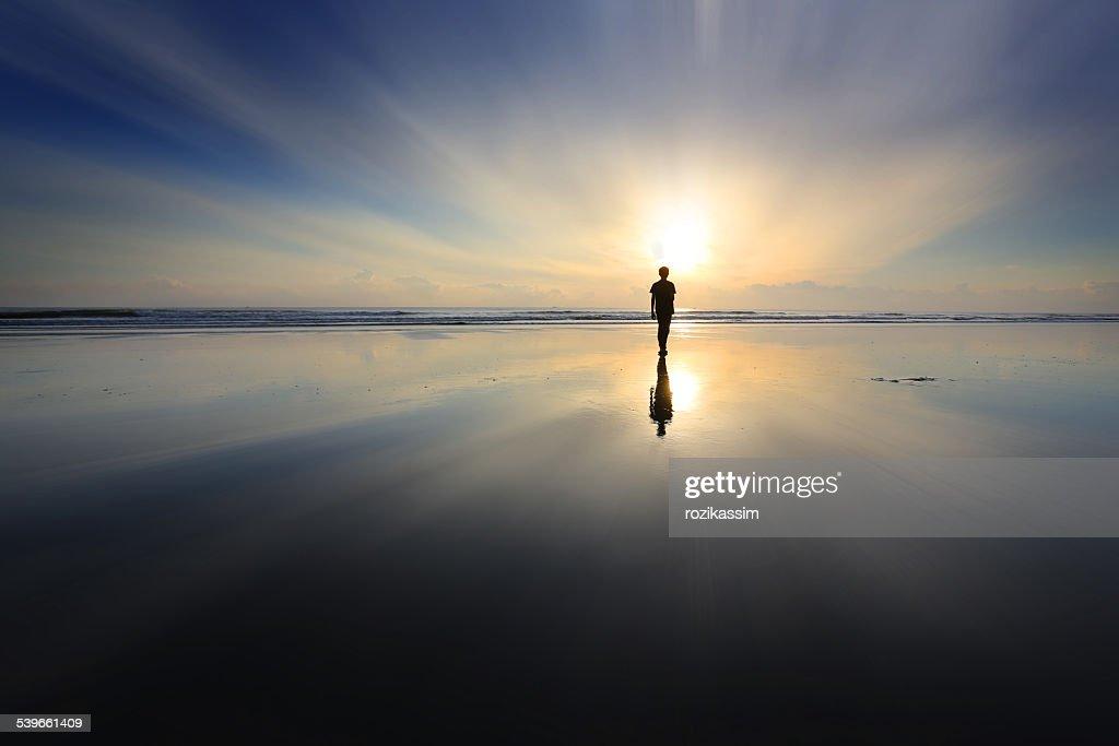 Boy walking on beach at sunset : Stock Photo
