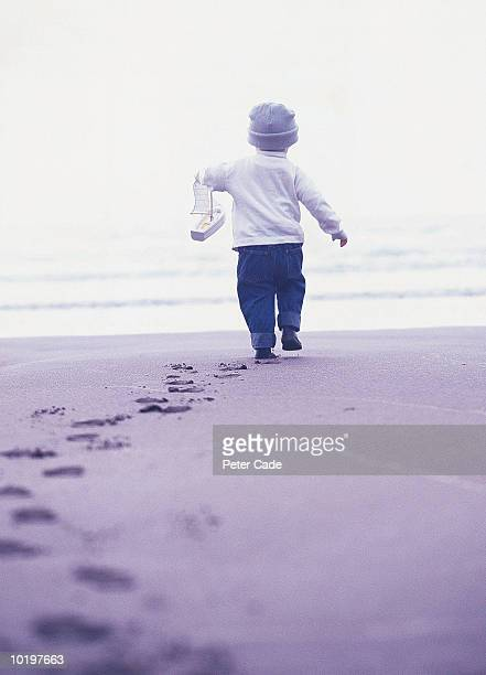 Boy (21-24 months) walking on beach holding toy boat, rear view