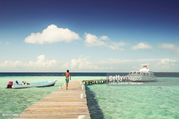 boy walking on jetty - belize stock pictures, royalty-free photos & images