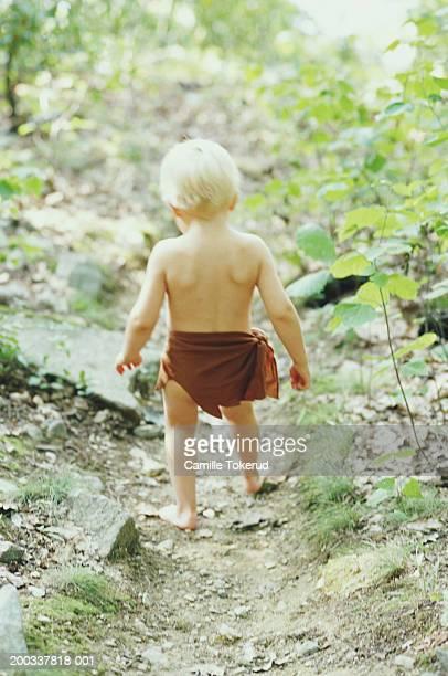 Boy (2-4) walking on path in woods, wearing loincloth, rear view