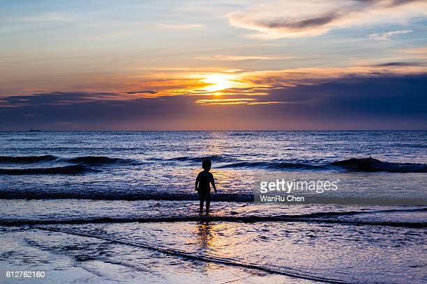 A boy walking on the beach at sunset