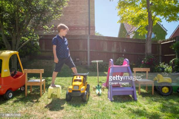 boy walking on toys arranged in yard - obstacle course stock pictures, royalty-free photos & images
