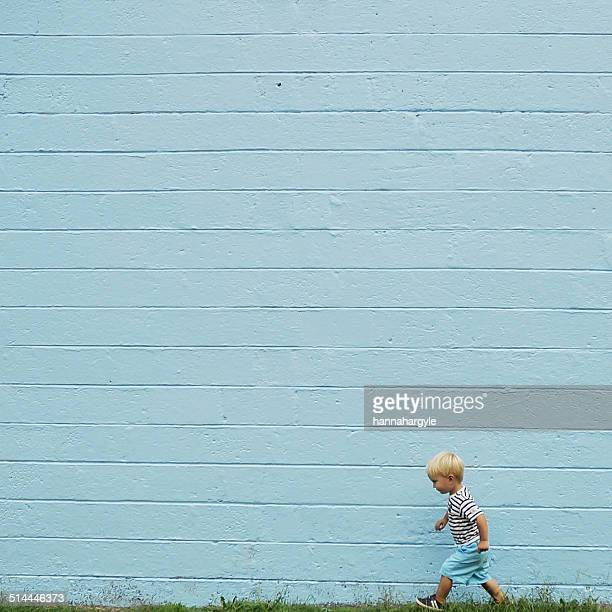 boy walking past a blue wall - striding stock pictures, royalty-free photos & images