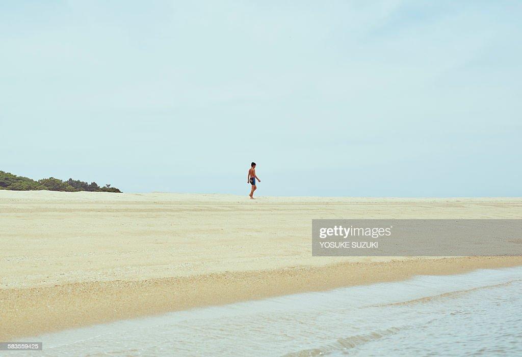 Boy walking the beach : Stock Photo