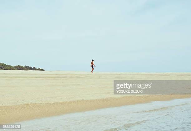 Boy walking the beach