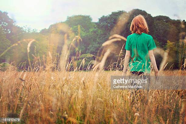 Boy walking through field
