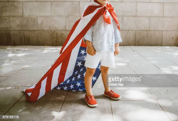 boy walking with american flag - month stock pictures, royalty-free photos & images