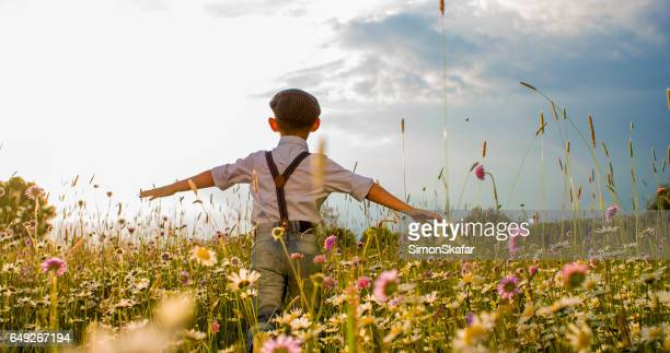 boy walking with arms outstretched on field - flat cap stock pictures, royalty-free photos & images