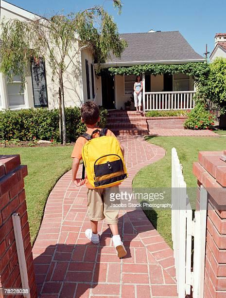Boy walking with book bag
