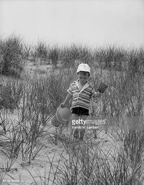 boy walking with bucket and spade  - {{relatedsearchurl(carousel.phrase)}} fotografías e imágenes de stock