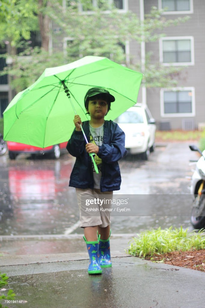 boy walking with green umbrella on street during monsoon stock photo