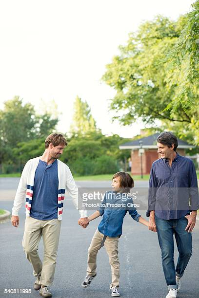 Boy walking with his fathers outdoors